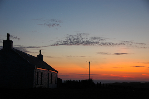 Picture of a colourful evening sky after sunset over a cottage