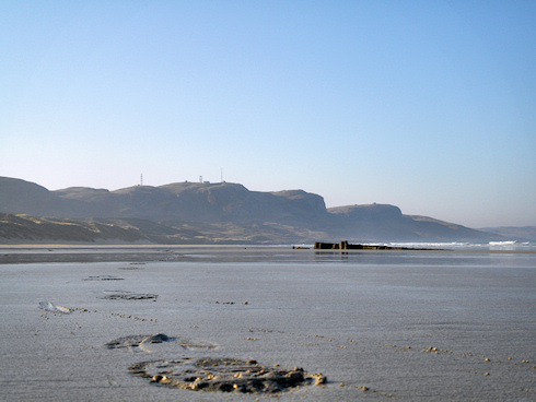 Picture of footsteps on a beach, a wreck and coastal hills in the background