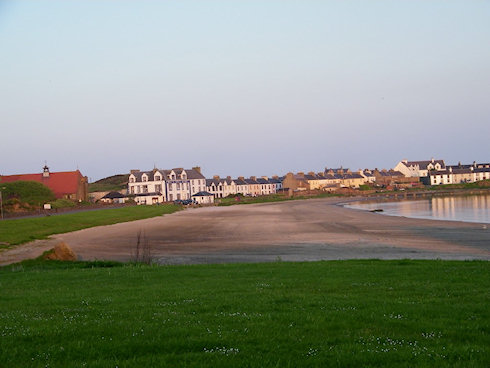 Picture of a wide beach with some houses behind