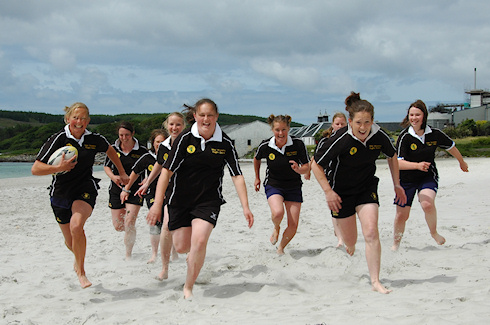 Picture of the Islay Womens Rugby Team running towards the camera on the beach in Port Ellen