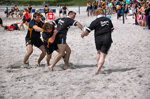Picture of four beach rugby players in action