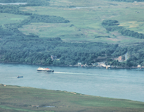 Picture of a Calmac ferry passing a small ferry port, seen from high above