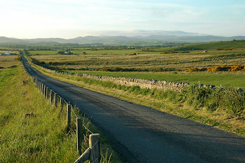 Picture of a single track road stretching in the distance on a sunny June evening