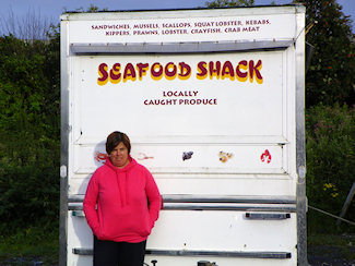 Picture of a trailer with the words Seafood Shack written on it, a woman standing in front of it