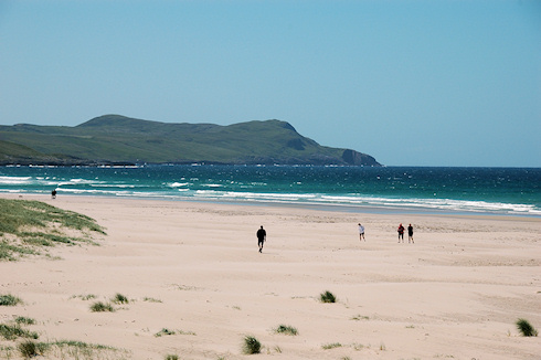 Picture of various people walking on a sandy beach in brilliant summer sunshine