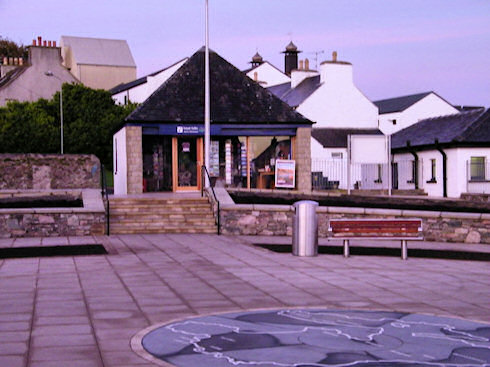 Picture from the centre of a village square, a map of Islay on the floor, tourist office in the background