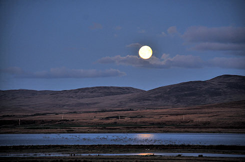 Picture of a moonrise over a sea loch, a hilly ridge behind it