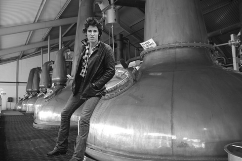 Picture of a row of stills with Bruce Springsteen standing in front of them