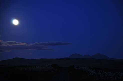 Picture of a moonlit landscape, looking along a road, distinctly shaped mountains in the distance on the right