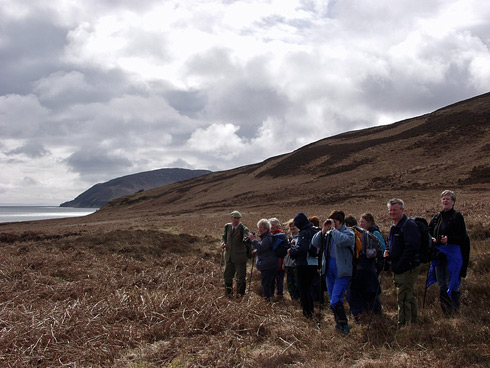 Picture of a group of walkers standing on a hillside of sound between two islands