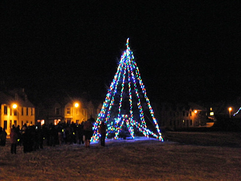 Picture of carol singers standing around a Christmas tree on a coastal village green