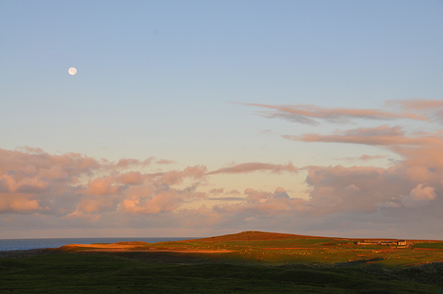 Picture of the moon over an island landscape in the morning sun