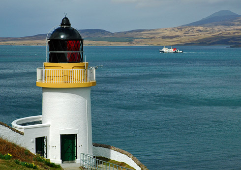 Picture of a lighthouse on a hillside above a sound, a Calmac ferry passing it