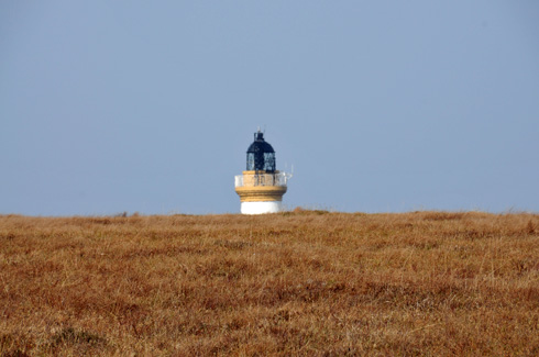 Picture of the top of a lighthouse appearing behind a hill