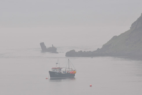 Picture of an anchored boat and a boat wreck on a very hazy day