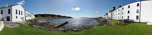 Picture of a panoramic view of a small sea loch, flanked by a distillery