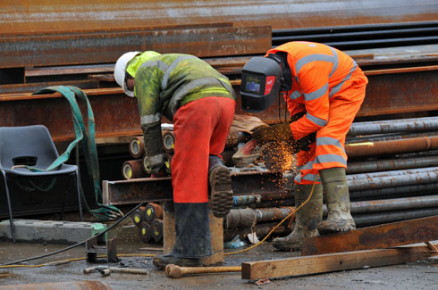 Picture of two workers grinding on a steel girder