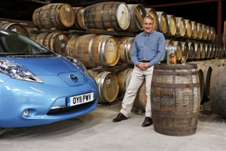 Picture of a car and a man in a whisky warehouse with many casks