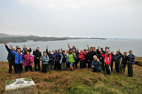Picture of a group of walkers on a small island, a larger island in the background