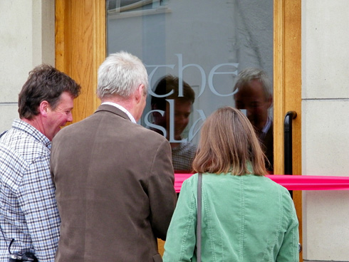 Picture of three people cutting the ribbon for a hotel called the islay