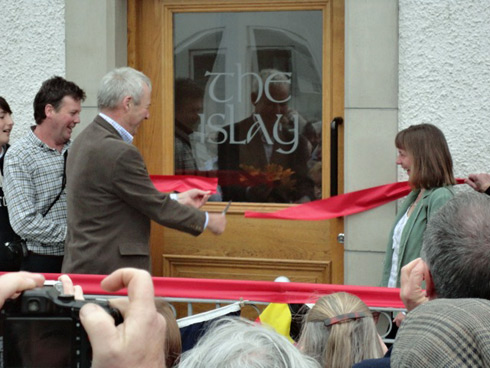 Picture of a man cutting the ribbon opening a hotel called the islay