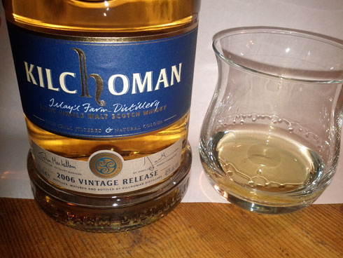 Picture of a Kilchoman 2006 vintage release with a poured dram next to it