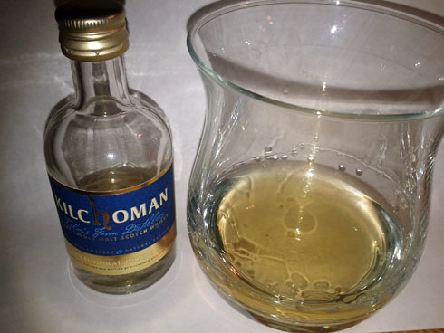 Picture of a miniature bottle of Kilchoman Inaugural Release Islay single malt whisky next to a whisky glass
