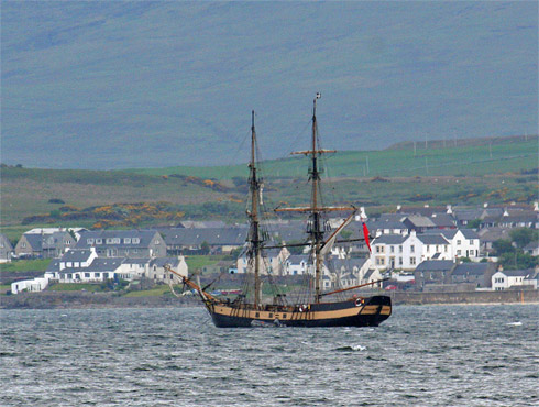 Picture of a tall ship anchored on a sea loch, just off a coastal village