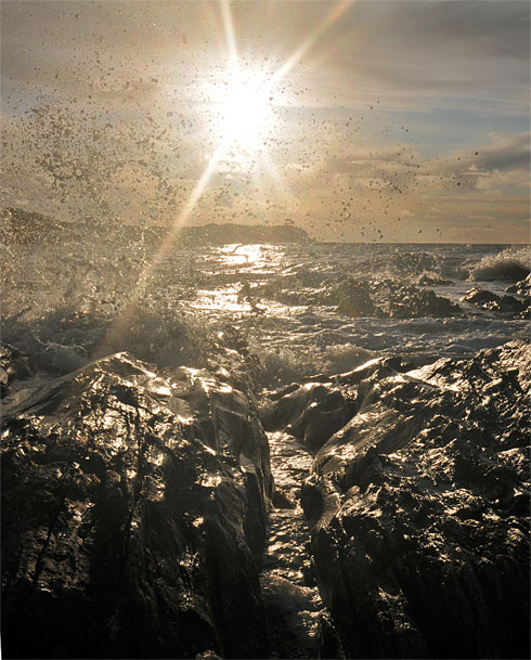 Picture of a wave splashing over rocks in a bay with the low sun in the background