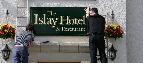 Picture of two men hanging a sign for The Islay Hotel