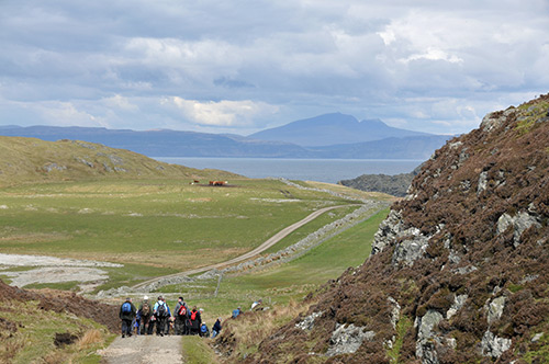 Picture of walkers on an island (Colonsay), another island visible in the distance