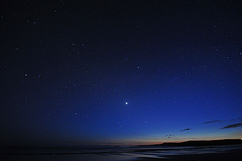 Picture of the sky over a beach in the last light, many stars starting to show