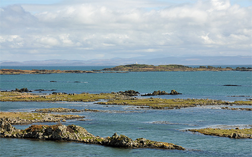 Picture of skerries off a coast, a lighthouse on one of them