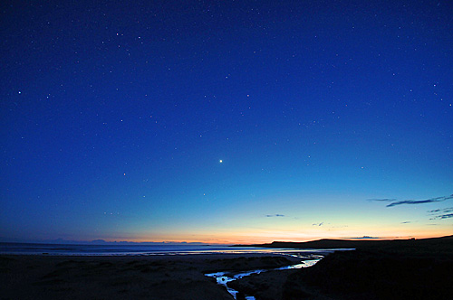 Picture of a beach in the gloaming, stars starting to appear in the sky