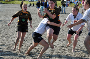 Picture of two ladies beach rugby teams in action
