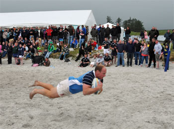 Picture of a player scoring a try in a beach rugby game