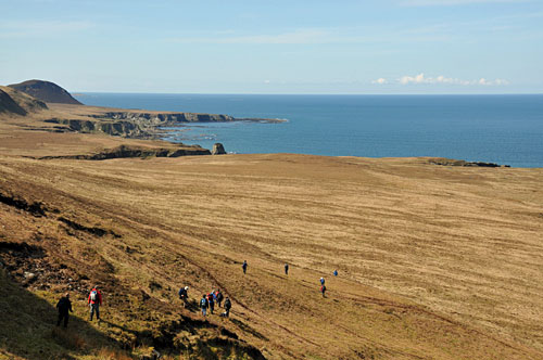 Picture of a group of walkers in a wide coastal landscape in the north of Islay