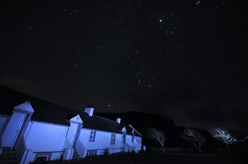 Picture of stars in the night sky over a row of cottages