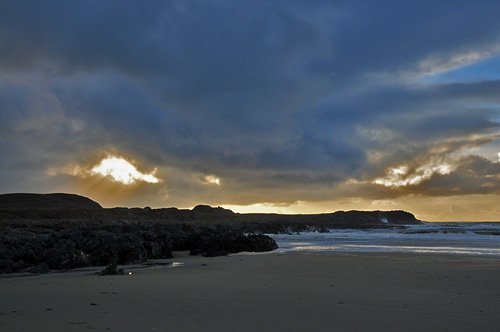 Picture of the sun breaking through some clouds over the cliffs of a sandy bay