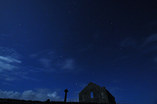 Picture of a church and a Celtic cross under a moonlit night sky