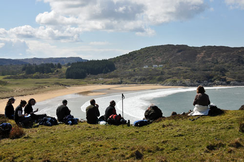 Picture of walkers having a lunch break high above a bay with a sandy beach