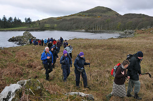 Picture of walkers next to a bay, a hill in the background