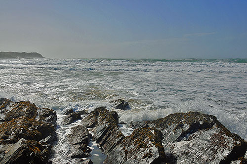 Picture of a bay with waves rolling in and on to a rocky shore