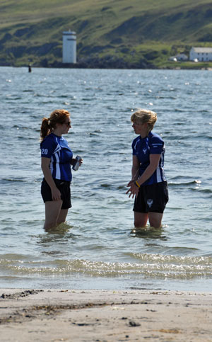 Picture of two female beach rugby players cooling down standing in the water, a lighthouse in the background