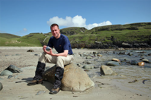 Picture of a man sitting on a rock on a beach with a Laphroaig hip flask in his hands