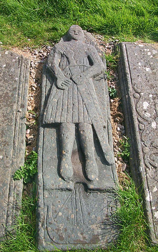 Picture of an ancient graveslab of a man in Highland armour