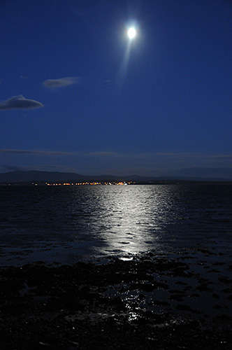 Picture of the Moon over a sea loch, reflecting in the loch. The lights of a village in the distance