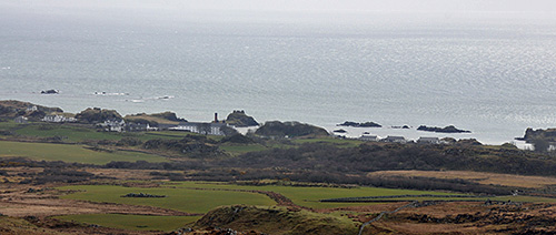 Picture of coastal village with a distillery, seen from coastal hills behind