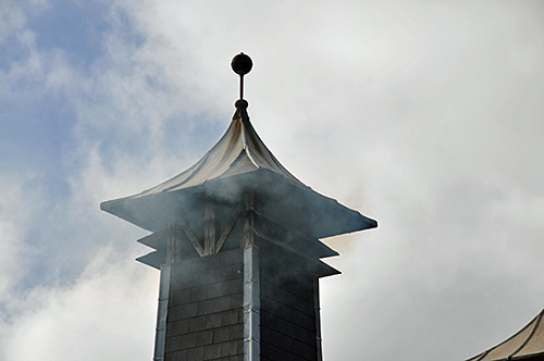Picture of a distillery pagoda with peat smoke coming out