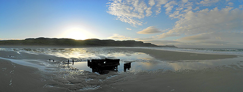 Panoramic picture of a sunrise over a bay with a sandy beach, a wreck in the sand